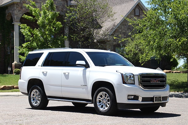 A white GMC Yukon delivered outside a happy customers's house as a part of the doorstep delivery program