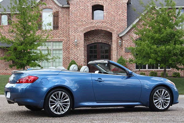 A blue infinity G37 delivered outside a happy customers's house as a part of the doorstep delivery program