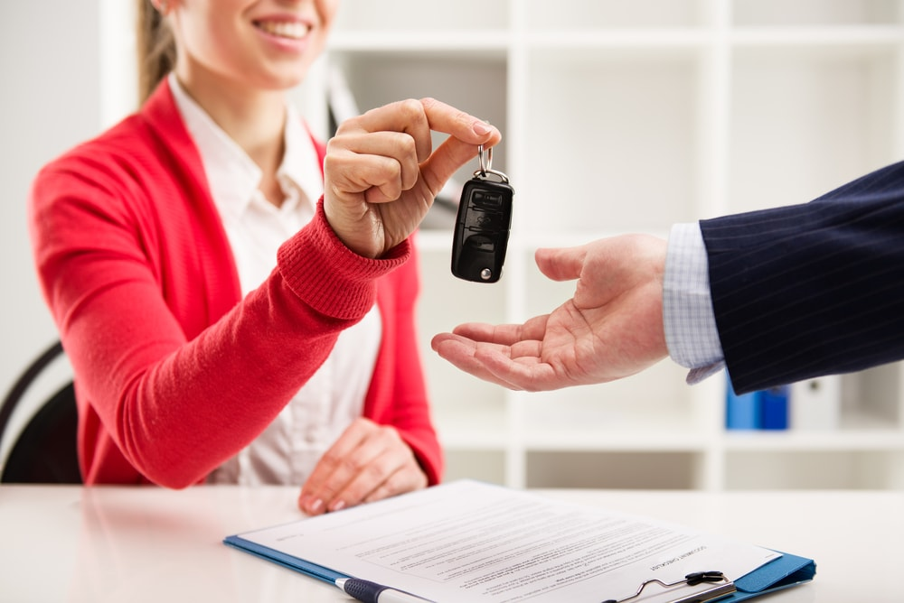 female sales representative handing keys to customer