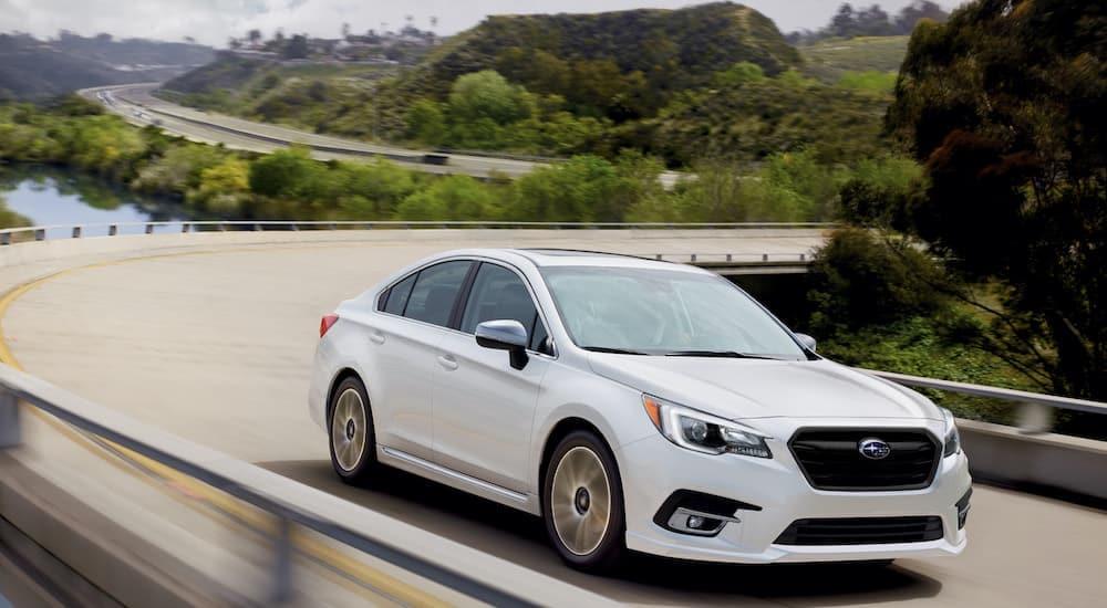 A white 2021 Subaru Legacy is shown driving down a winding bridge after leaving a Subaru Legacy dealer.