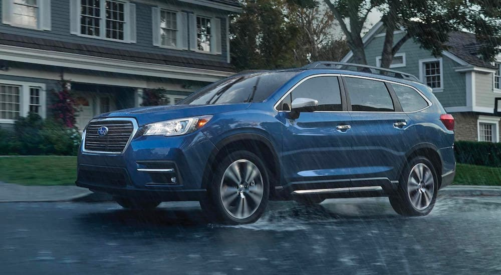 A blue 2021 Subaru Ascent is shown from the side driving in the rain after leaving a Subaru dealership.