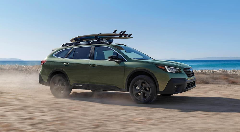 A green 2021 Subaru Outback is driving on a dirt road past the ocean.