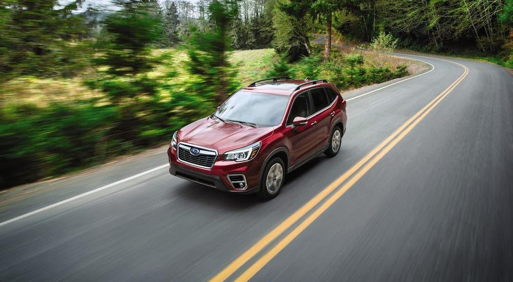 A red 2021 Subaru Forester is driving on a road in the woods after leaving a Subaru Dealer in New Jersey.