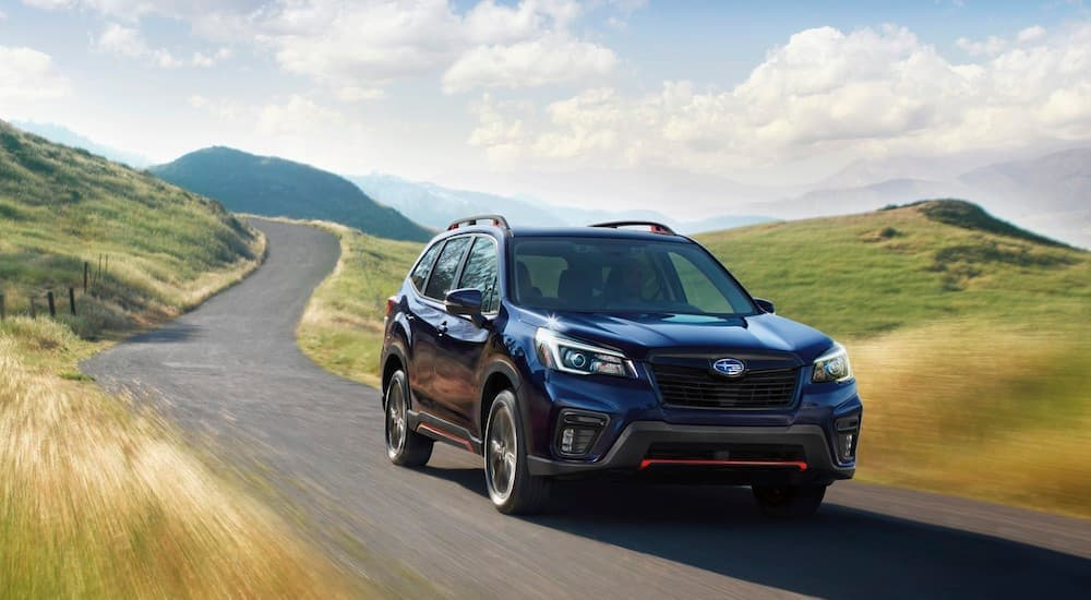 A dark blue 2021 Subaru Forester is shown driving past rolling hills and grass.