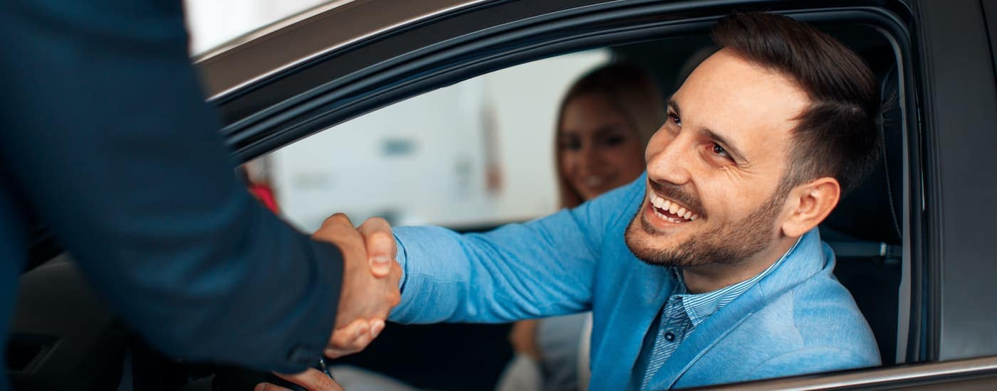 A man is shaking hands with a salesperson at a Staten Island Subaru dealer.