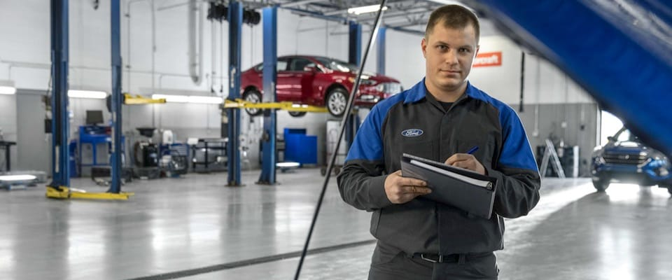 A Ford mechanic holding a clipboard