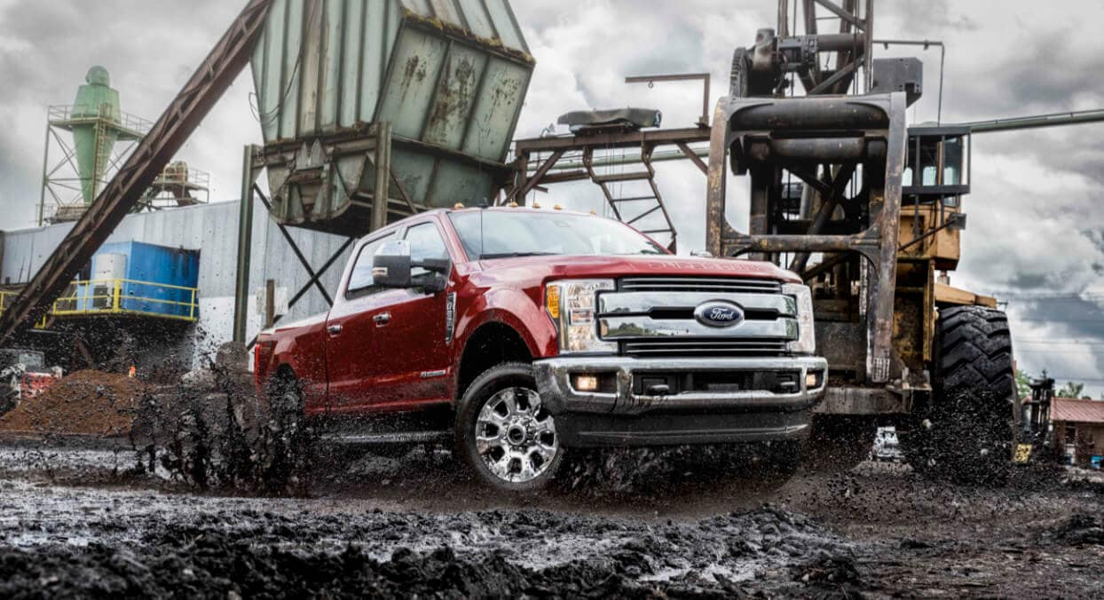 2020 Ford Super Duty Lariat in red driving through thick mud