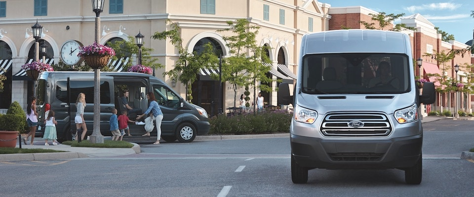 A silver 2019 Ford Transit driving through the town center