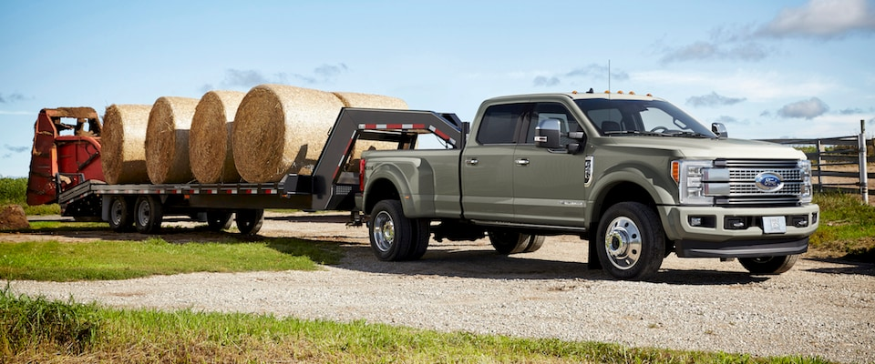 A Ford Super Duty towing a bunch of hay bales