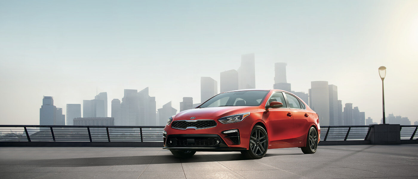 2020 Kia Forte in red parked on look out with city skyline behind it