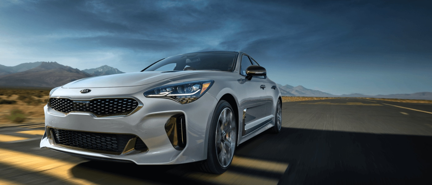 2019 Kia Stinger in white driving on highway away from the mountians