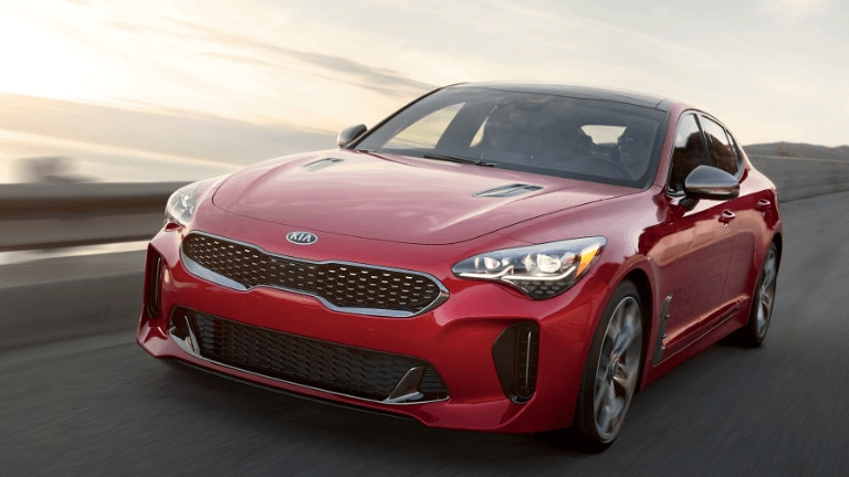 2019 Kia Stinger in red driving on coastal highway