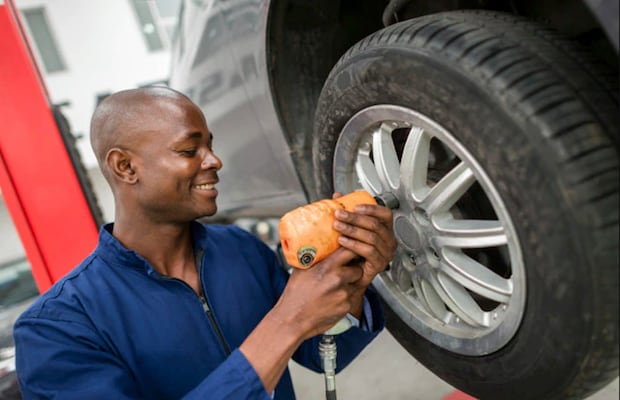 A Ford Service Technician working on changing a tire