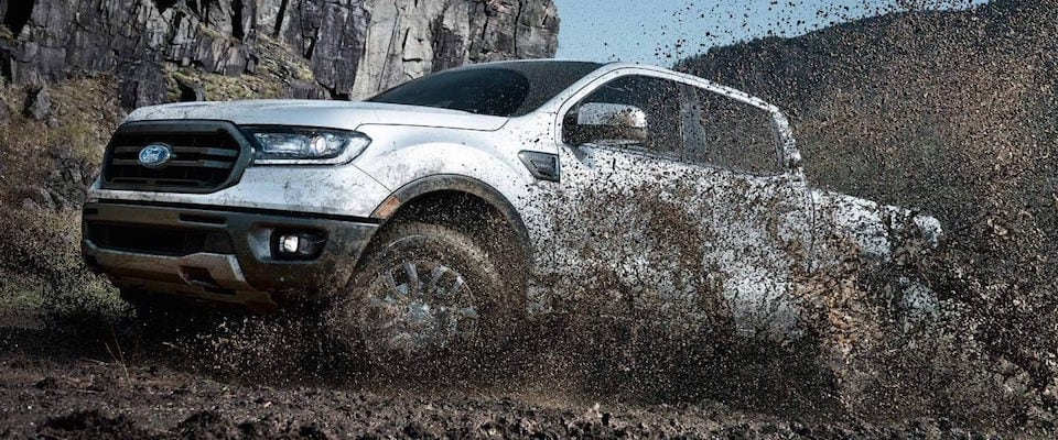 A 2019 white Ford Ranger off roading in the mud