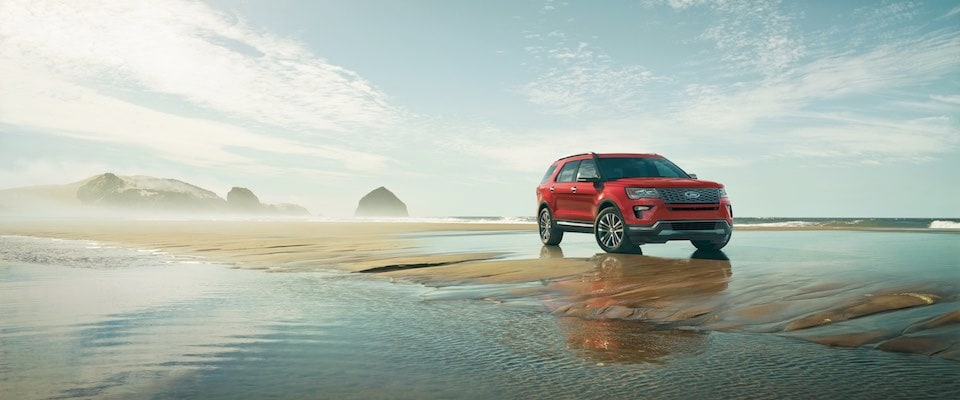 A red 2019 Ford Explorer parked on a beach