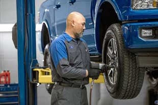 A Ford service technican changing a tire on a blue Ford F-150
