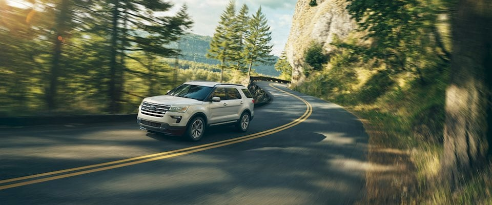 A white 2019 Ford Explorer driving through a forest