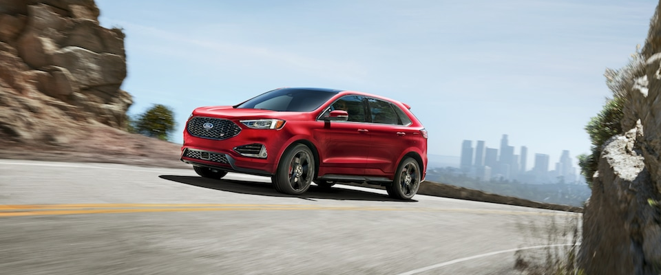 A Red  Ford Edge Driving Down An Open Road On A Sunny Day