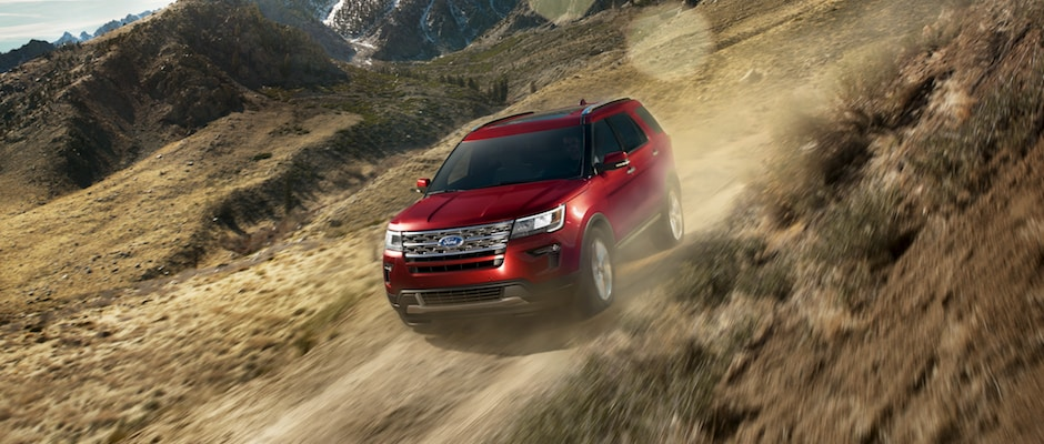 A red Ford Explorer driving through the mountains