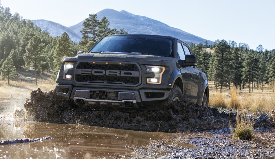A 2018 Ford F-150 Raptor driving through the mud