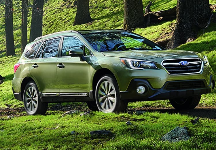2019 Subaru Outback driving through a forst trail