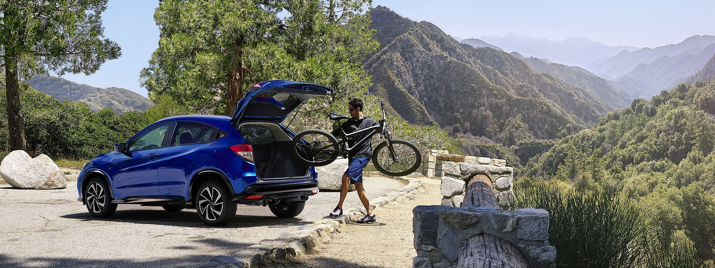man loading a bicycle into the back of a blue 2019 HR-V
