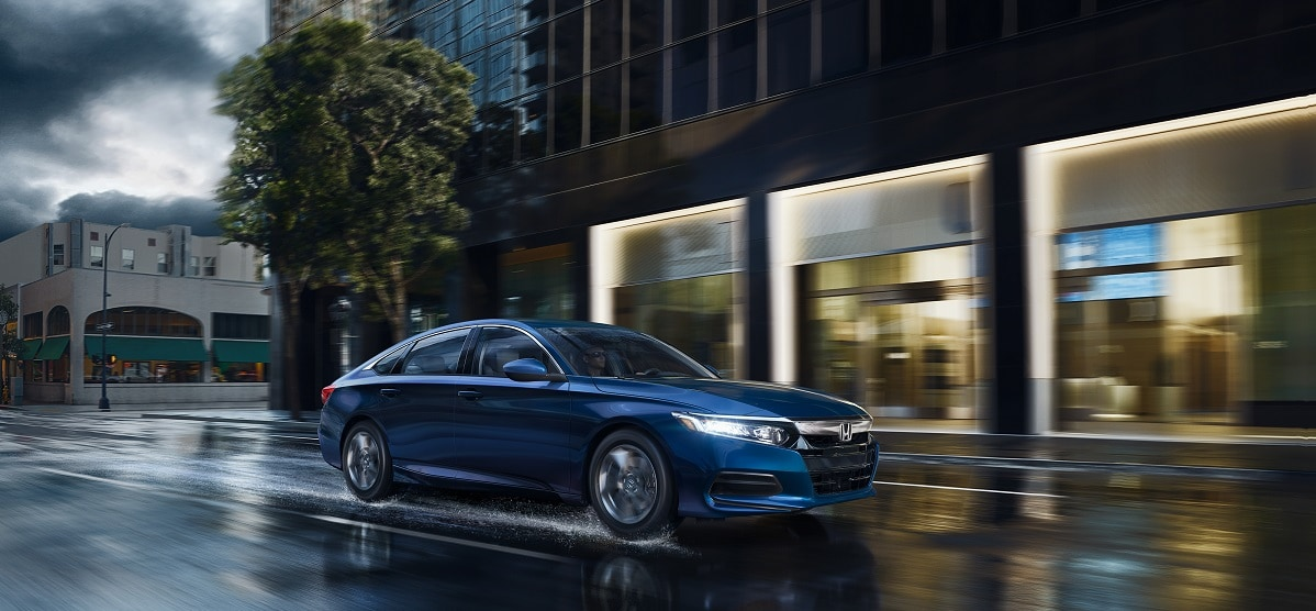 blue 2019 honda accord driving on a wet road