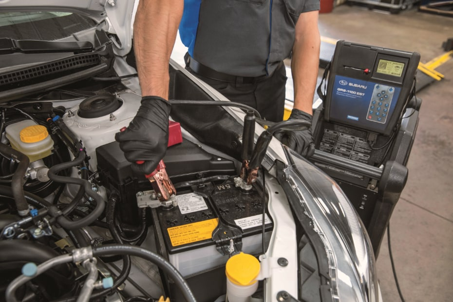 Subaru Technician Tests a Battery in a Subaru Service Department