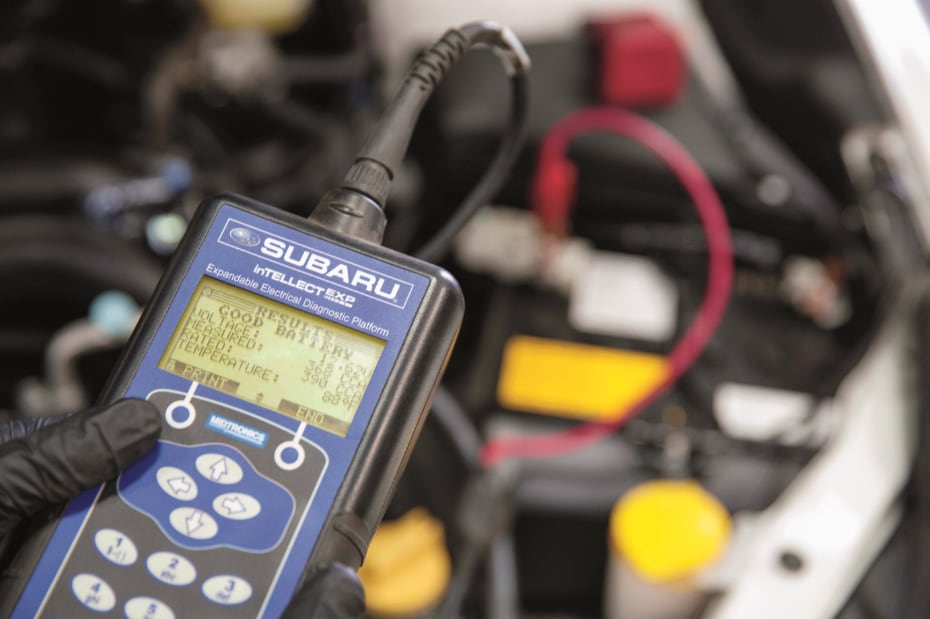 Subaru Service Technician Using a Diagnostic Tool on a Subaru Battery