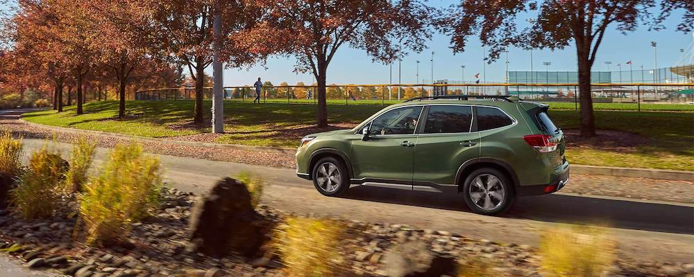 2020 Subaru Forester driving by a sports field