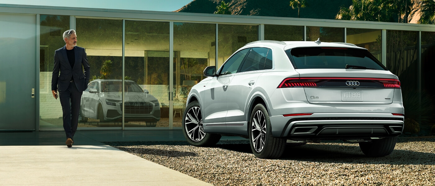 Man walking to 2020 Audi Q8 Parked outside his house