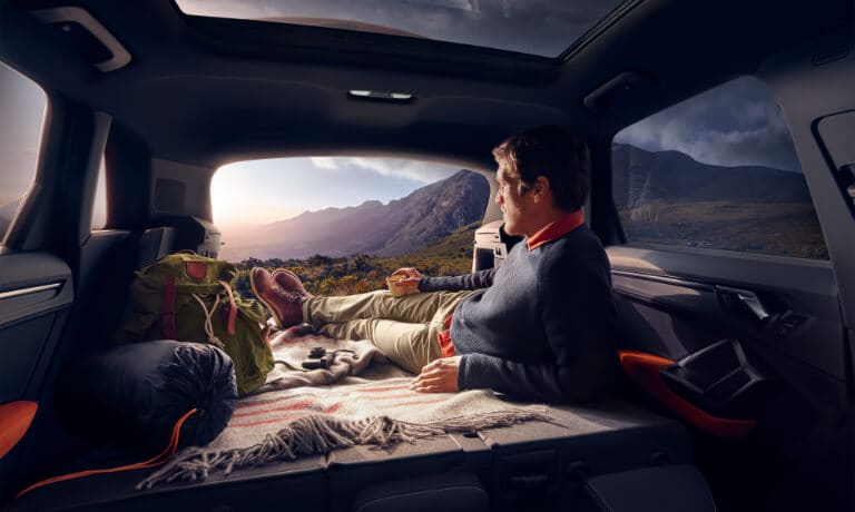 2020 Audi Q3 Interior back seats folded down while man lays down and watches the sunset