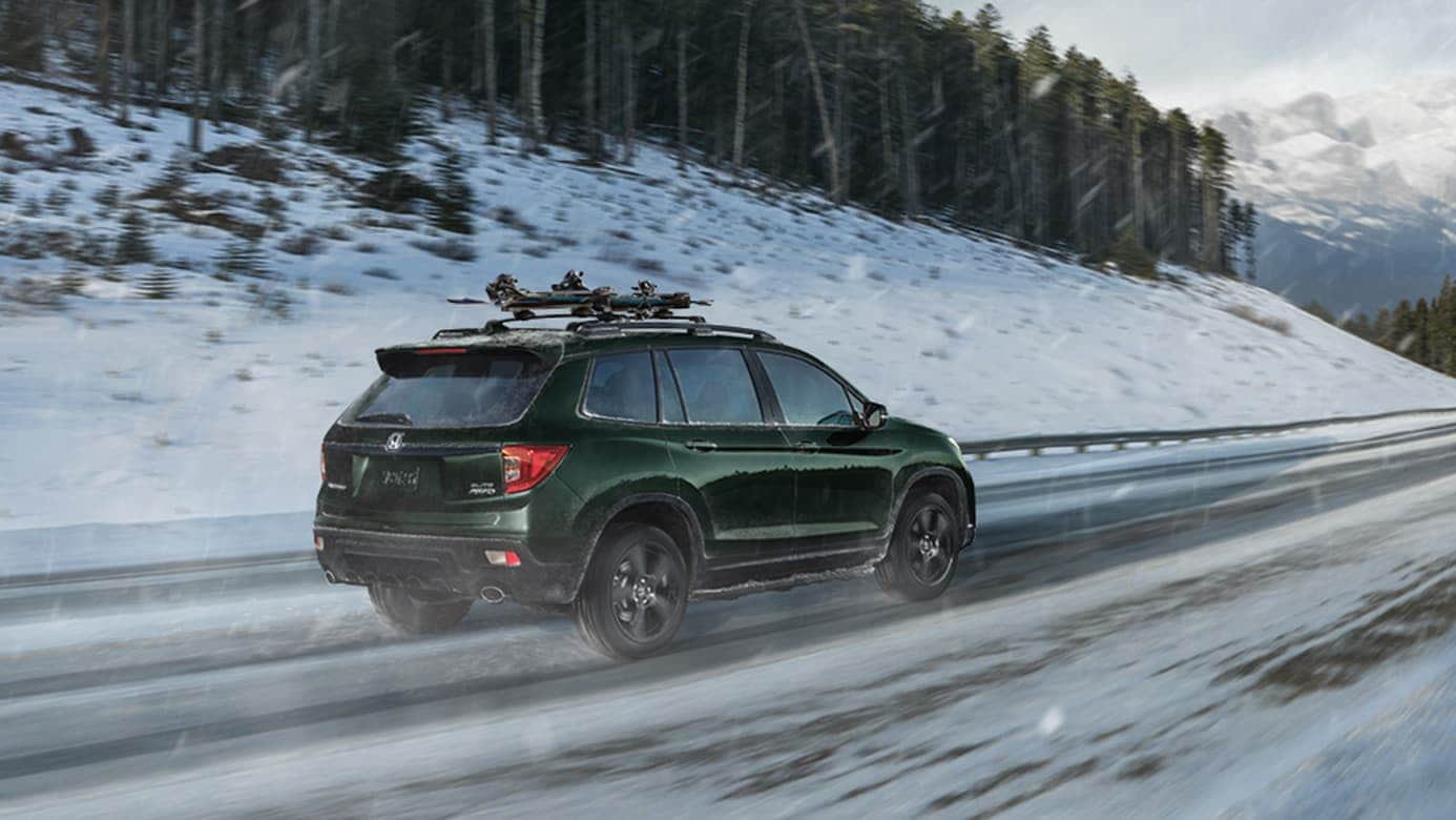 2019 Honda Passport in green driving on snowy road