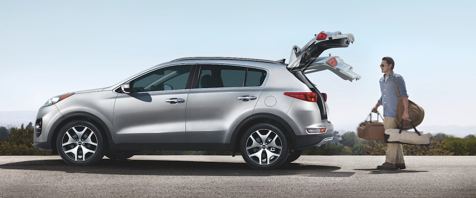 Man putting his backs in the back of a silver 2019 Kia Sportage