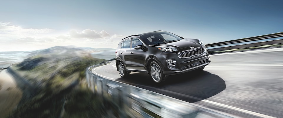 A black 2019 kia Sportage driving around a curve on an open highway