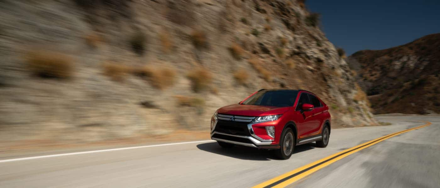 Red 2019 Mitsubishi Eclipse Cross driving down hill