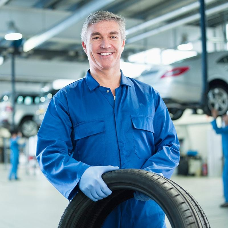 automotive technician smiling and holding a tire