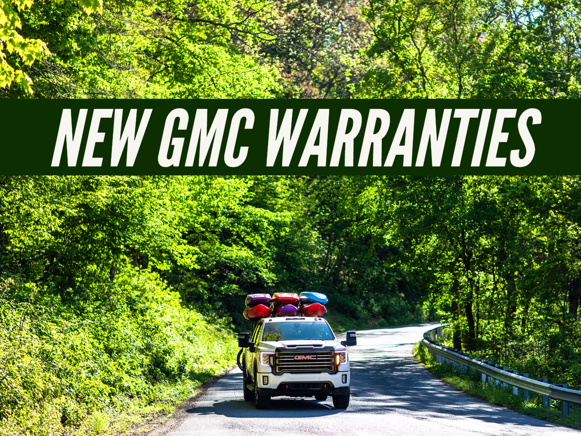"""""""New GMC Warranties"""" on Photo with new GMC Sierra At4 driving down wooded road"""