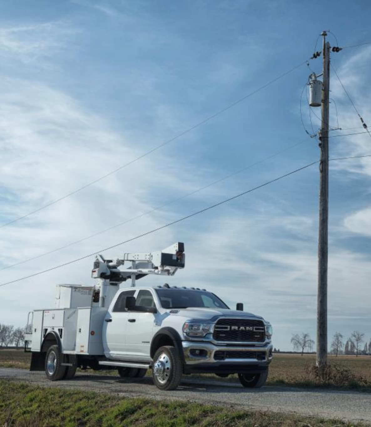 Parked Ram truck with lifting mechanism upfit next to phone pole