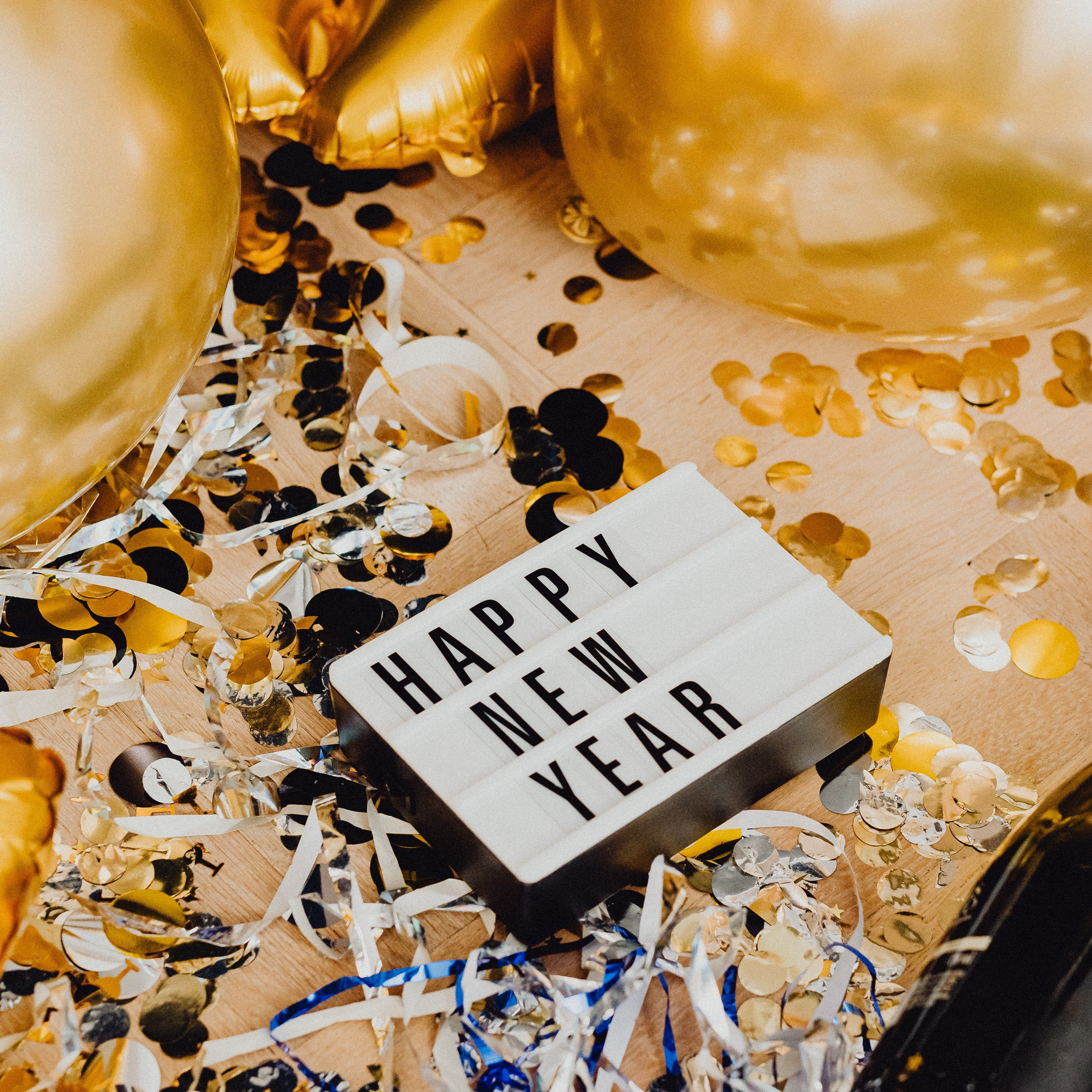 Happy New Year Sign with Gold balloons and confetti
