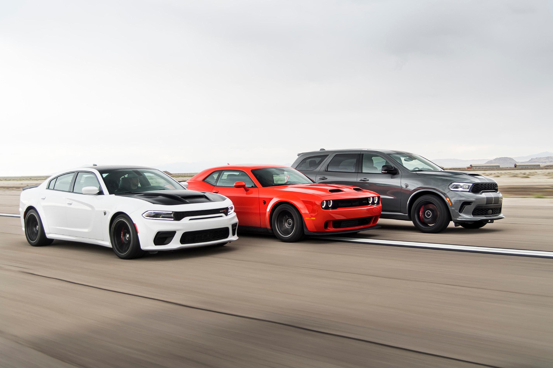 White Dodge Charger, Red Dodge Challenger, Dark Grey Dodge Durango driving next to each other