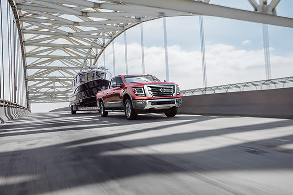 New 2020 Nissan Titan XD driving over a bridge towing a boat