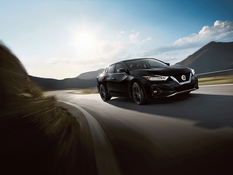 New 2020 Nissan Maxima black exterior driving on country road