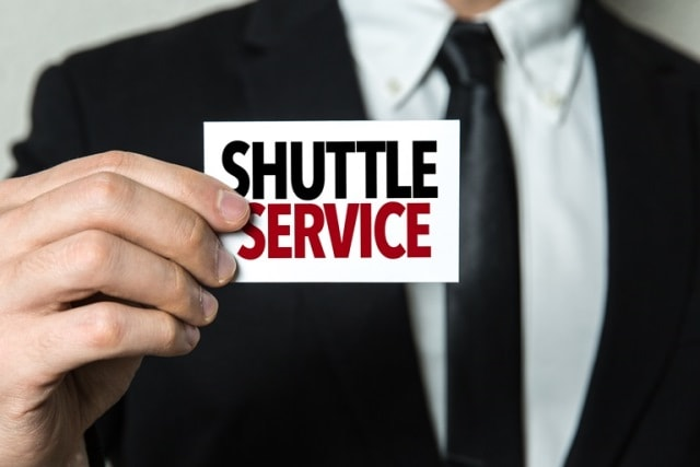 Man holding a shuttle service sign