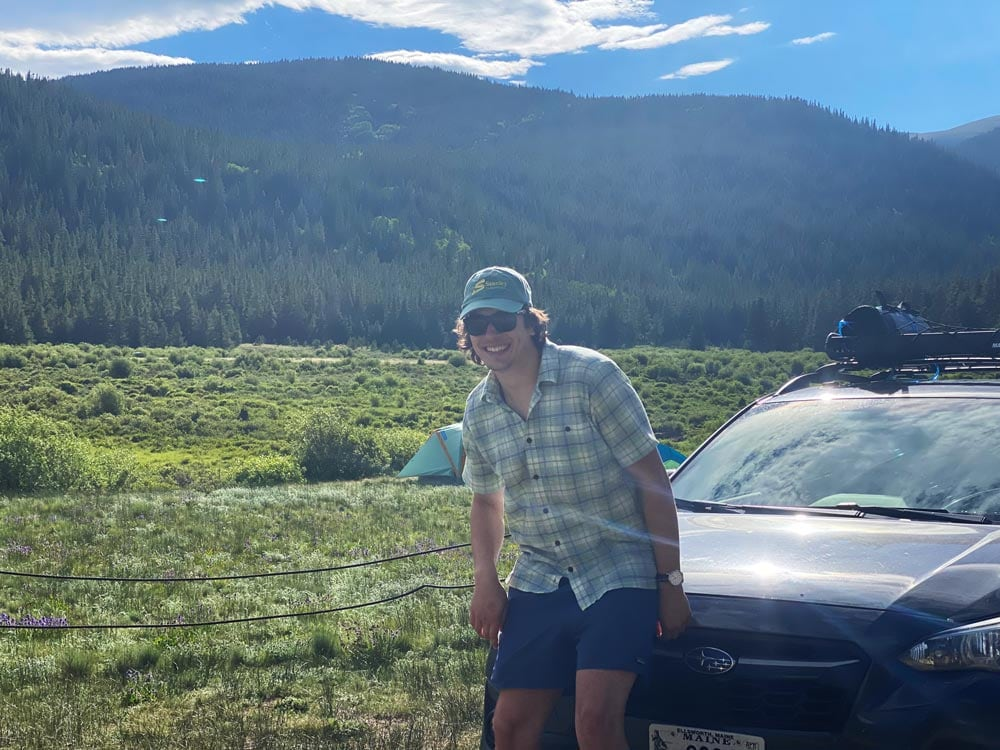 Jack, wearing a Stanley Subaru hat, on his Crosstrek in front a beautiful view of a lea and low mountain