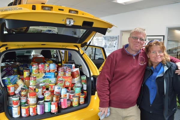 Neil and Jen next to a literal carful of donated food