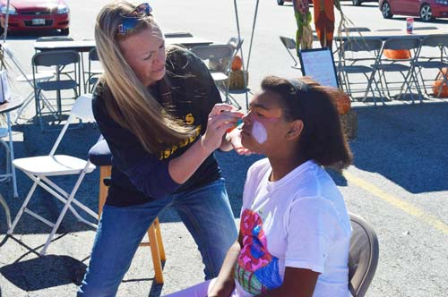 A young girl getting her face painted at Autumn Gold