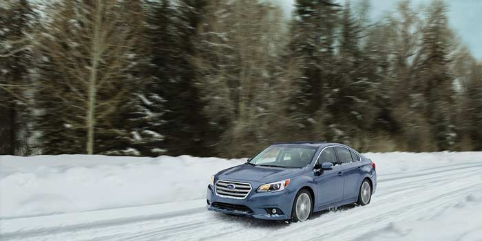 Subaru Legacy driving through the  snow backed by tall conifers and blue sky