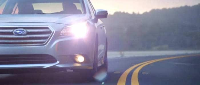 Subaru Legacy on the road near the  water, dusk with headlights on