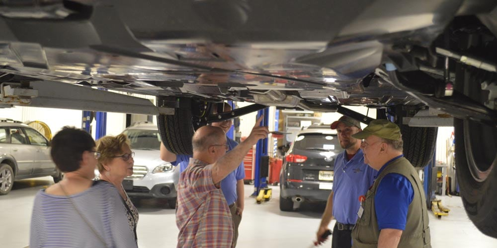 Our Certified Master Technician with some guests looking at the underside of a Subaru